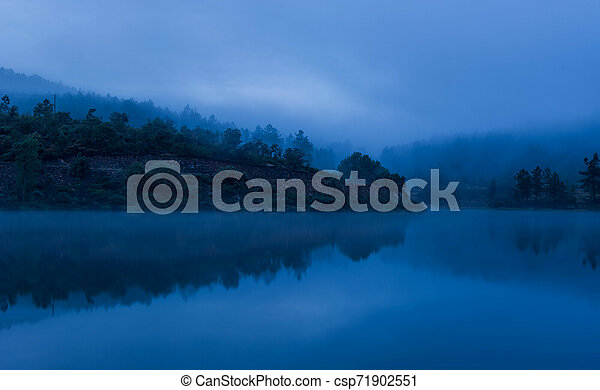 Misty lake with reflections and forest - csp71902551