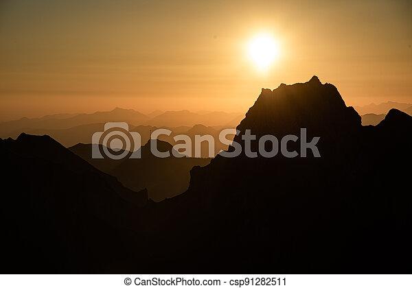 Misty sunset with beautiful silhouette of mountain range in Switzerland - csp91282511