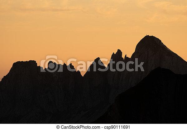 Misty sunset with beautiful silhouette of mountain range in Switzerland - csp90111691