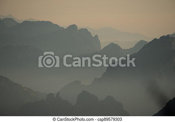 Misty sunset with beautiful silhouette of mountain range in Switzerland - csp89579303