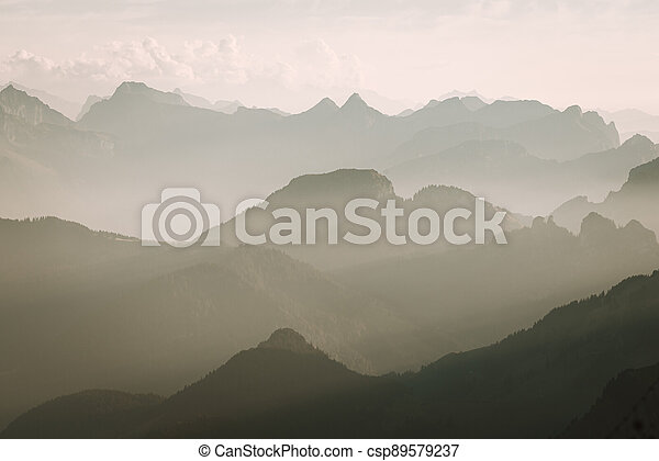 Misty sunset with beautiful silhouette of mountain range in Switzerland - csp89579237
