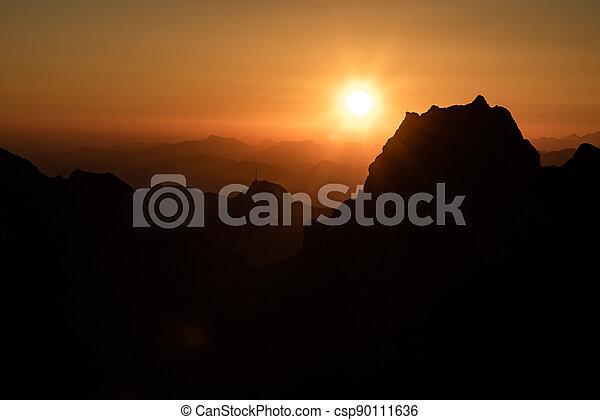Misty sunset with beautiful silhouette of mountain range in Switzerland - csp90111636
