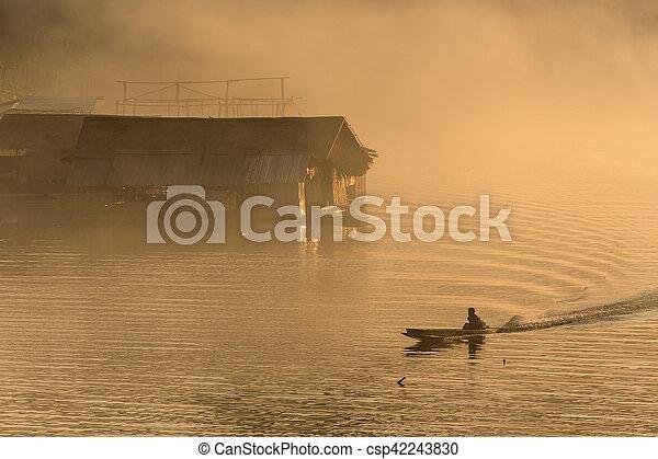 Misty tropical sunset on lake - csp42243830