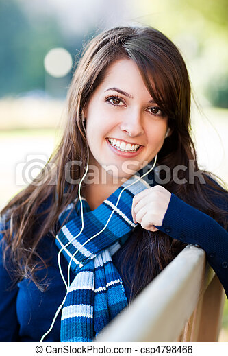 Mixed race college student listening to music - csp4798466