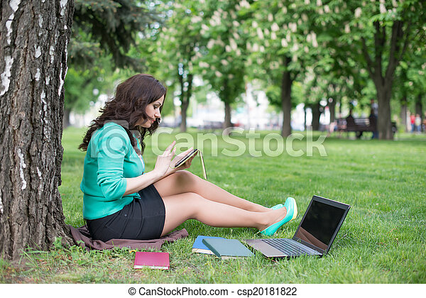 Mixed race college student sitting on the grass working - csp20181822