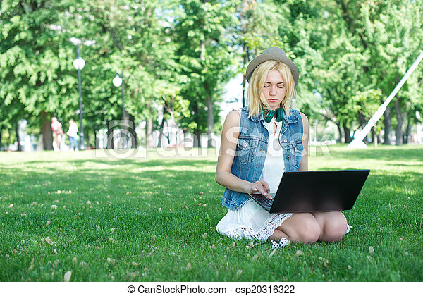 Mixed race college student sitting on the grass working - csp20316322