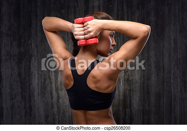 Mixed race sporty woman with dumbbells demonstrating back muscles - csp26508200