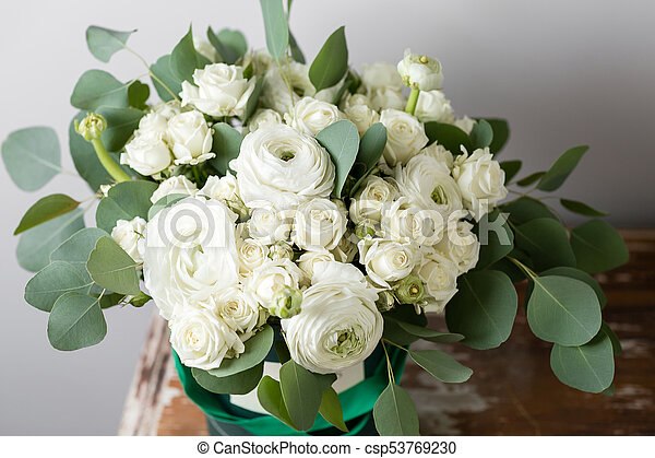 Mixed white flowers bouquet of spray roses and ranunculuses in a mixed white flowers bouquet of spray roses and ranunculuses in a box on wooden table mightylinksfo