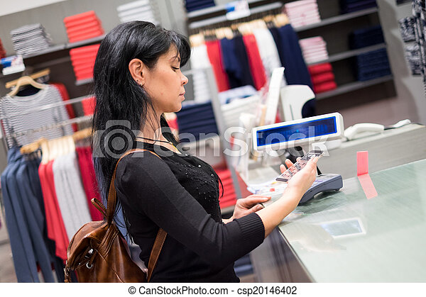 Mobile payment. Girl pays to shop using mobile phone - csp20146402