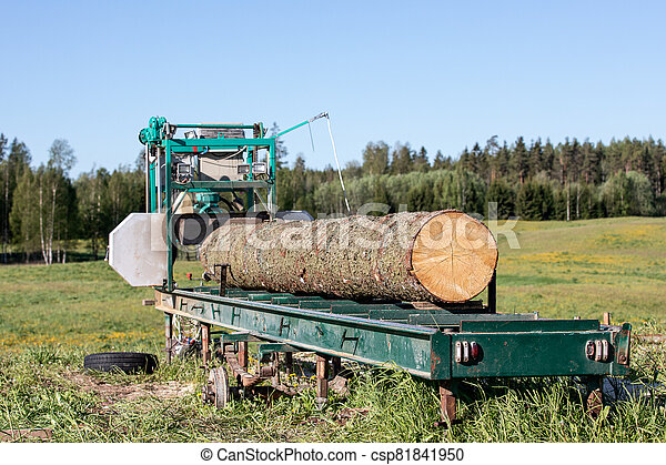 Mobile sawing equipment for logs in the open air. Rural landscape on a sunny day - csp81841950