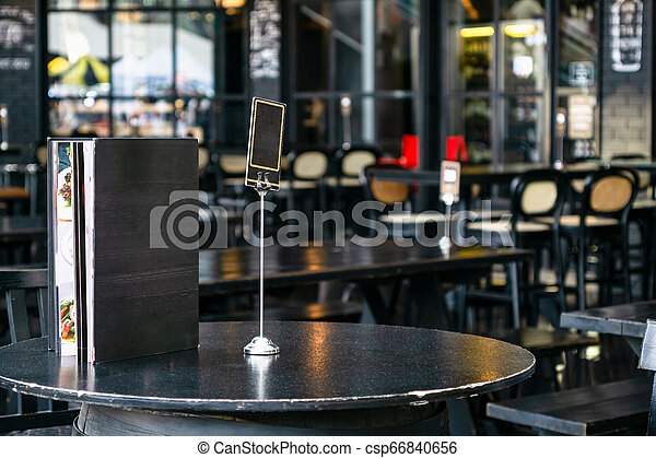Mock up blank cover menu frame on the blurred background of outdoor coffee and restaurant terrace with tables and chairs . - csp66840656