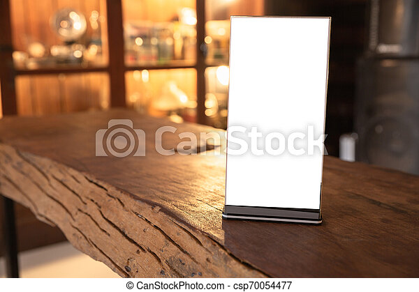 Mock up Menu frame in Bar restaurant, Stand for booklets with white sheets of paper acrylic tent card on wooden table on cafeteria blurred background. - csp70054477