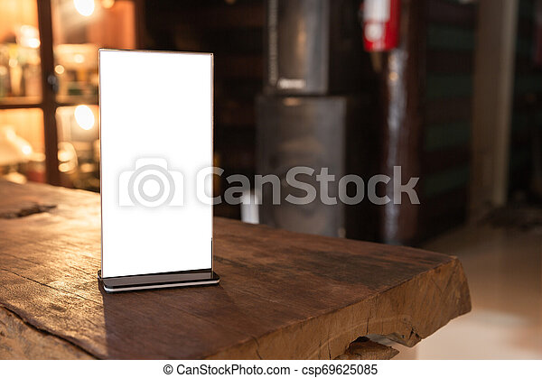 Mock up Menu frame in Bar restaurant, Stand for booklets with white sheets of paper acrylic tent card on wooden table on cafeteria blurred background. - csp69625085
