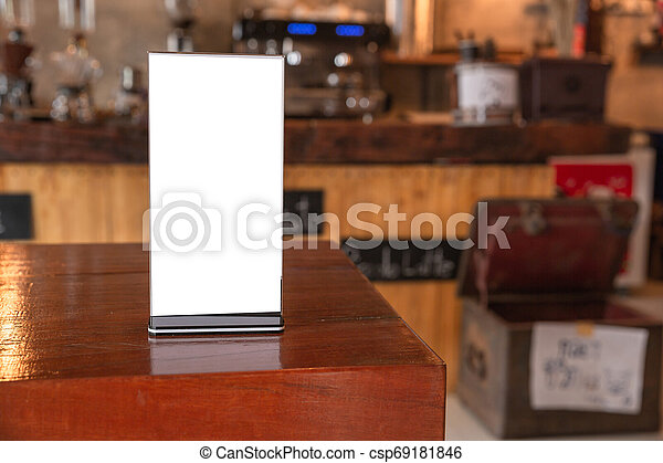Mock up Menu frame in Bar restaurant, Stand for booklets with white sheets of paper acrylic tent card on wooden table on cafeteria blurred background. - csp69181846