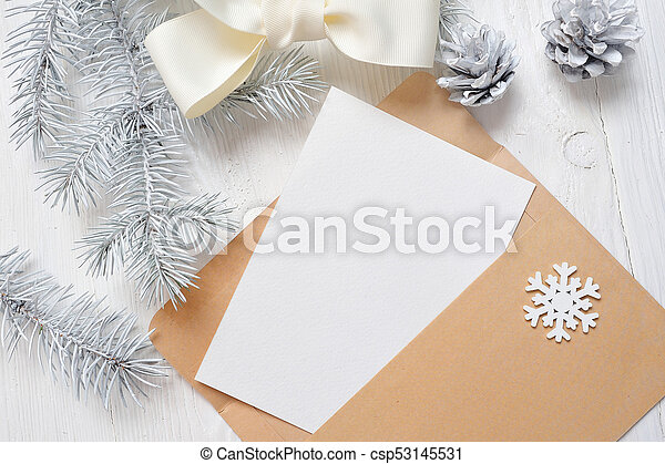 Mockup Christmas greeting card letter in envelope with white tree and cone, flatlay on a wooden background, with place for your text - csp53145531