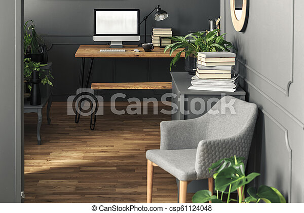 Mockup of computer desktop on wooden desk in workspace interior with grey armchair. Real photo - csp61124048