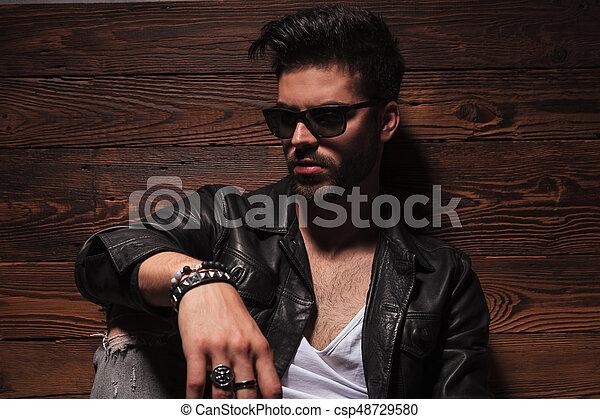Hombre de moda triste con gafas de sol y chaqueta de cuero