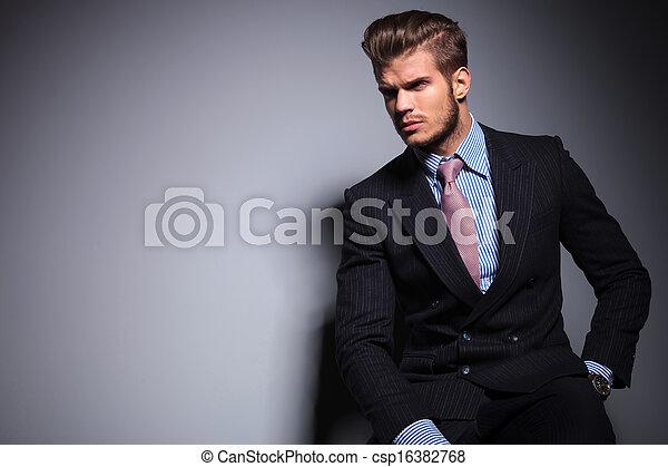 Modelo de moda sentado en traje mira hacia otro lado - csp16382768