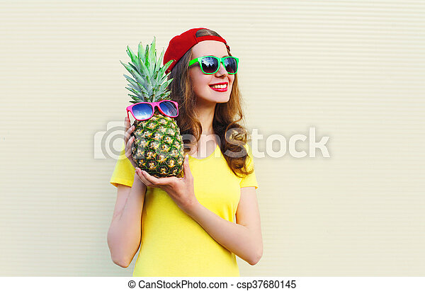 Una chica sonriente con piña sobre fondo blanco - csp37680145