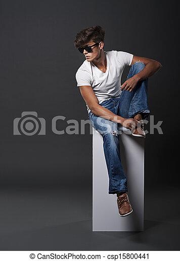 Un joven de moda sentado en un rectángulo blanco - csp15800441
