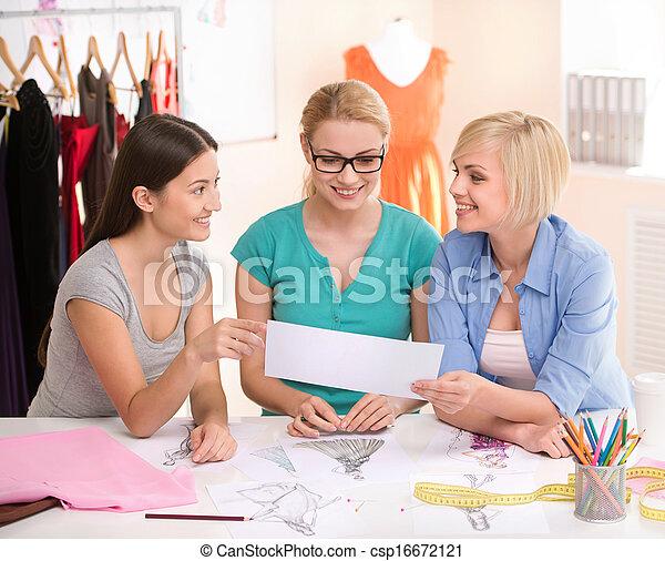 Diseñadores de moda en el trabajo. Tres alegres jóvenes trabajando en el estudio de diseño de moda - csp16672121