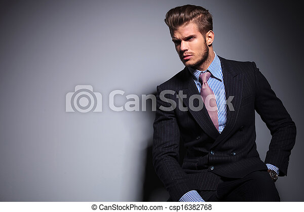 Seated young fashion model in suit look away - csp16382768