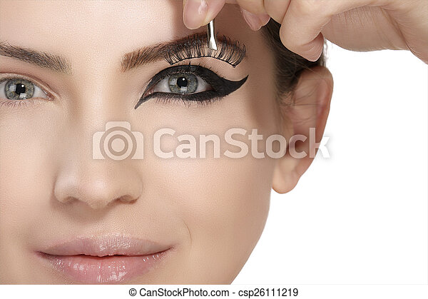 Model applying artificial eyelashes extension on smoky eye - csp26111219