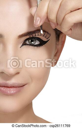 Model applying artificial eyelashes extension on smoky eye - csp26111769