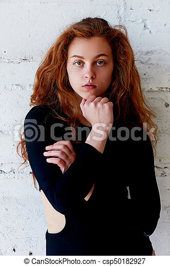 Model Tests Beautiful Redhead Girl With Curly Hair Natural Color Krupneishego Portrait On A Background Of Light Brick Wall