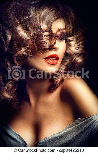 Chica sexy. Modelo de belleza posando sobre fondo oscuro - csp34425310