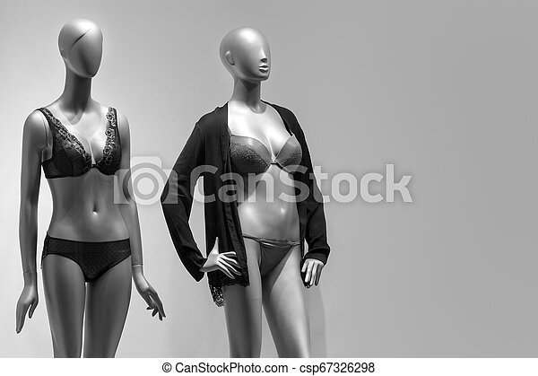 Modern and luxury shop of underwear. Full-length female mannequins in nderwear. Lingerie on plastic dolls in store window display. Sale and advertising theme. Copyspace for text - csp67326298
