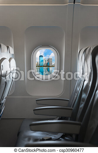 Modern city skyline through window on a commercial airliner aircraft. - csp30960477