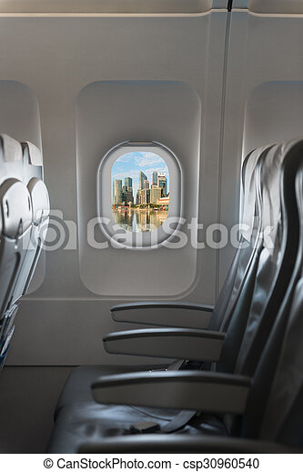 Modern city skyline through window on a commercial airliner aircraft. - csp30960540