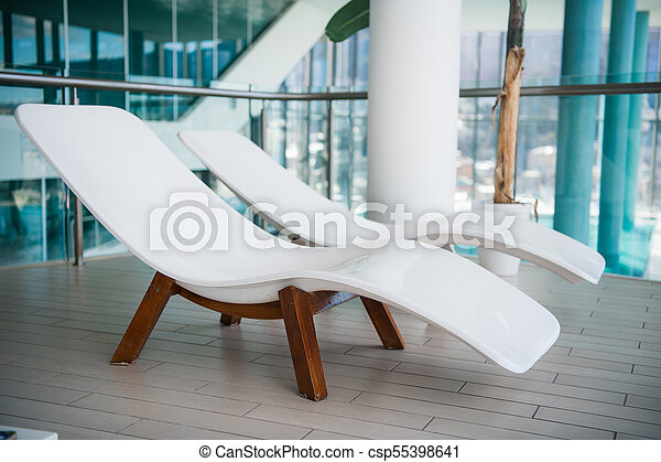 Modern deck chairs at luxury hotel. Private swimming pool for relaxation,  with beautiful interior.