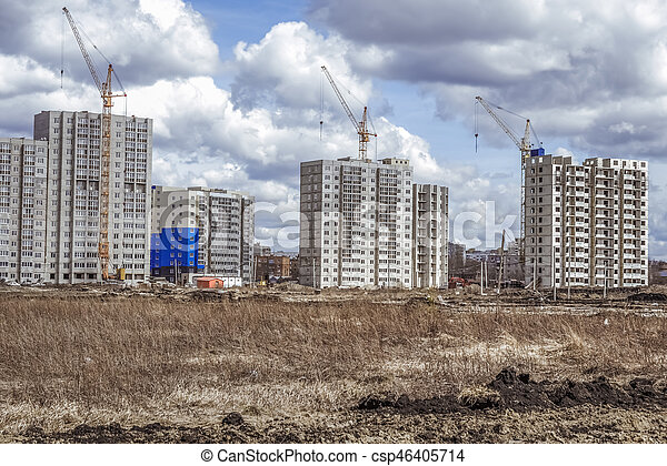 Modern houses under construction and construction cranes - csp46405714