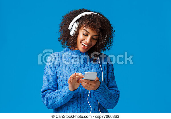 Modern lifestyle, technology and urban concept. Attractive hipster girl african american woman in winter sweater, afro haircut, wearing headphones and messaging using smartphone, smiling - csp77060363