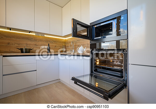 Modern White And Beige Wooden Kitchen Interior With Oven Opened Well Designed White And Wooden Beige Modern Kitchen Interior Canstock