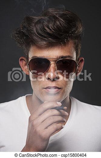 Un joven elegante inhalando humo de cigarrillo - csp15800404