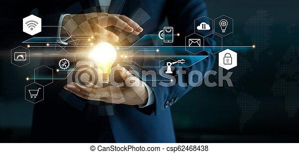 El concepto de innovación empresarial. La mano del hombre de negocios sosteniendo una bombilla brillante con conexión de la red de tecnología de iconos. Mercadeo digital futurista y desarrollo innovador en la interfaz moderna. - csp62468438