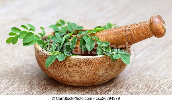 Moringablätter und Mörserpestle - csp26394379