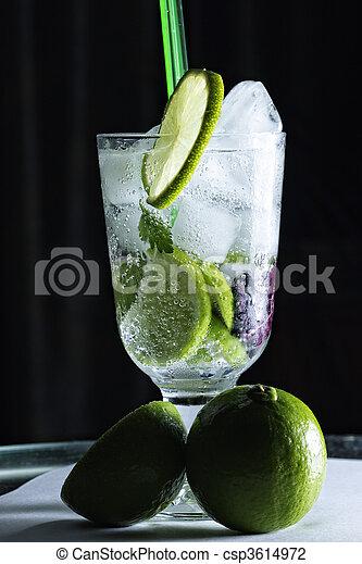 Mojito cocktail and limes against dark - csp3614972
