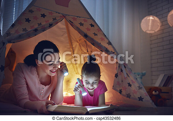Family bedtime mom and child daughter are reading a book mom and child daughter are reading a book with flashlights in tent csp43532486 sciox Gallery
