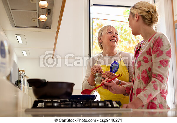 mom and daughter cooking in home kitchen - csp9440271