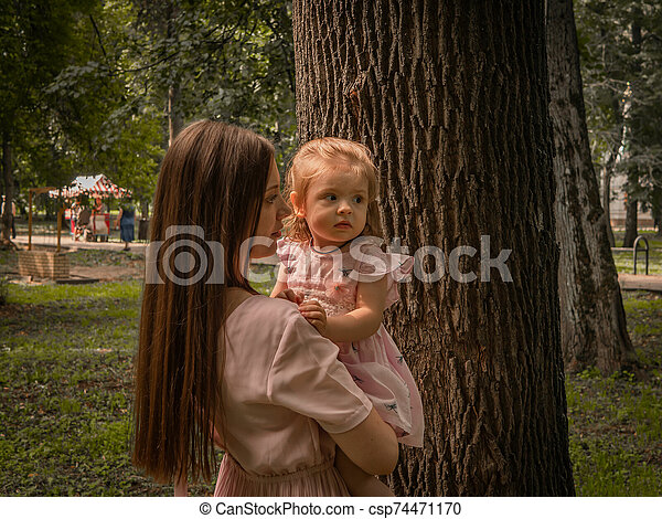 Mom and daughter walk and play in the park. Dressed in dresses. Sunny day, weekend in a city park. - csp74471170