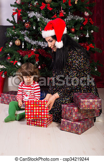 Mom and toddler son opening christmas gifts. Mother and toddler son ...