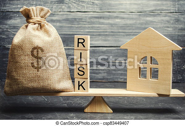 Money bag, blocks with the word Risk and a wooden house on the scales. The concept of losing money when investing in real estate. Risks of losing a home or housing for non-payment. Property insurance - csp83449407