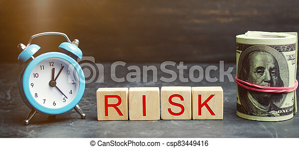 Money, clock and wooden blocks with the word Risk. The concept of financial risk. Justified risks. Investing in a business project. Making the right decision. Property insurance. Legal / market risks - csp83449416
