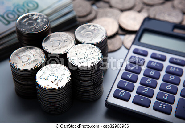 money in the form of banknotes and coins with calculator - csp32966956