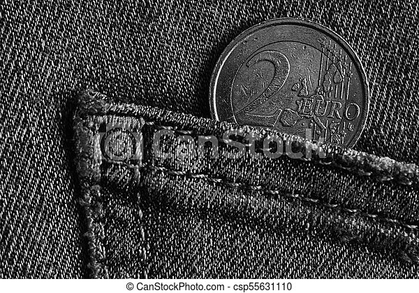 Monochrome Euro coin with a denomination of 1 euro in the pocket of blue denim jeans - csp55631110