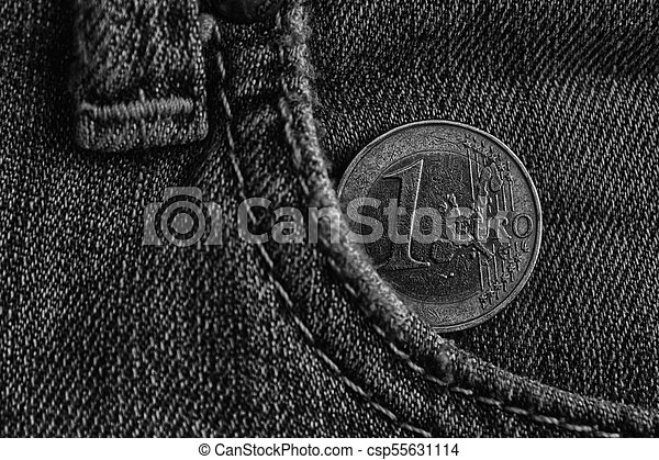 Monochrome Euro coin with a denomination of 1 euro in the pocket of blue denim jeans. - csp55631114